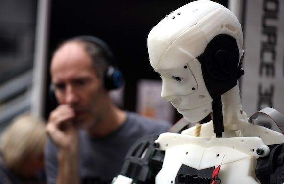 An employee talks to a voice activated InMoov robot, made from 3-D printed parts, during the 3-D Print show at the Business Design Center in London, U.K., on Friday, Nov. 8, 2013. Popularity for 3-D printers has increased among engineers, designers and manufacturers as prices have fallen, making them affordable to more consumers. Photographer: Chris Ratcliffe/Bloomberg via Getty Images
